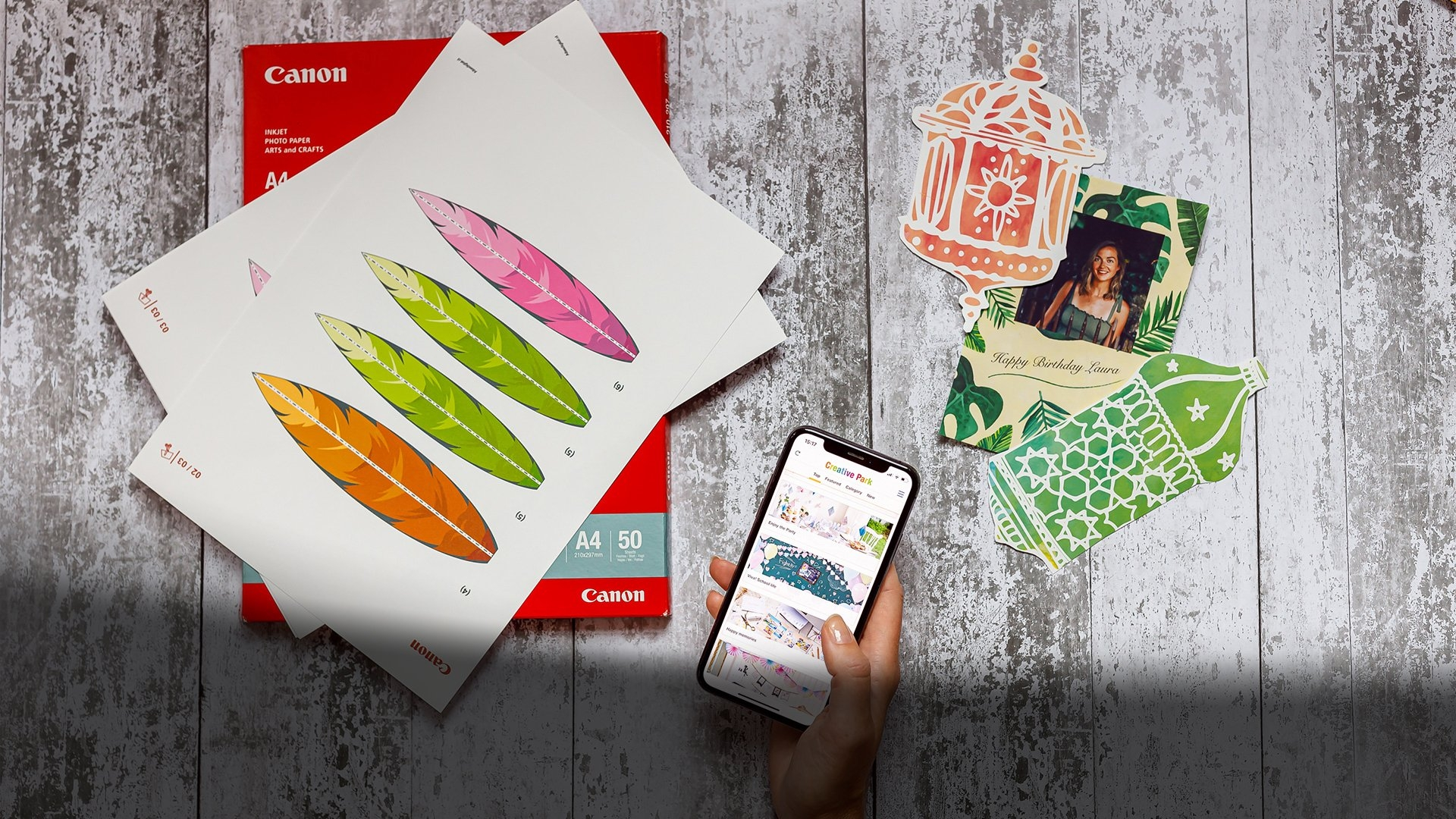 A hand holding a smartphone displaying the Creative Park app. Canon printer paper and Creative Park templates and designs are arranged on the table.